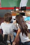 Écoliers à l'aide de la Tablette de Digital dans la salle de classe Photographie stock libre de droits
