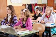 Écoliers à la salle de classe pendant une leçon Image stock
