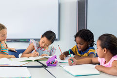 Écoliers écrivant sur des livres Photographie stock
