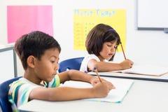 Écoliers écrivant sur des livres Images libres de droits