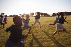 Écoliers élémentaires et filles courant dans un domaine ouvert Photos libres de droits