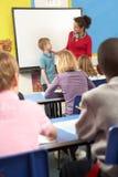 Écoliers étudiant dans la salle de classe avec le professeur photos stock