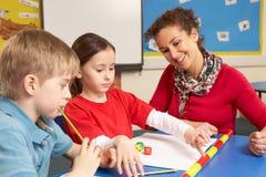 Écoliers étudiant dans la salle de classe avec le professeur Photographie stock