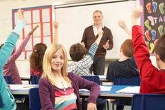 Écoliers étudiant dans la salle de classe avec le professeur Photos libres de droits