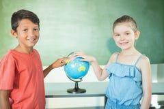 Écoliers étudiant le globe dans la salle de classe Photo libre de droits