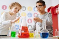 Écoliers agréables sentant la chaleur rayonner du flacon chimique Photographie stock libre de droits