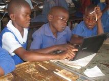 Écoliers apprenant à utiliser des ordinateurs Photos libres de droits
