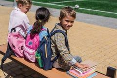 Écoliers avec des livres se reposant sur le banc Photo libre de droits