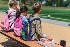 Écoliers avec des livres se reposant sur le banc Photographie stock libre de droits