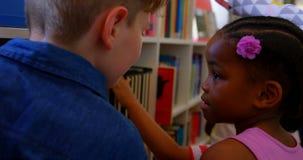 Écoliers choisissant un livre dans une bibliothèque à l'école 4k banque de vidéos