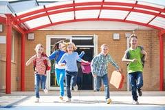 Écoliers courant dans le terrain de jeu à l'extrémité de la classe Image libre de droits