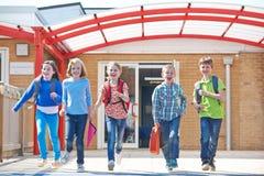 Écoliers courant dans le terrain de jeu à l'extrémité de la classe Photographie stock