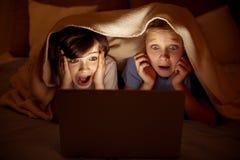 Écoliers craintifs observant le film effrayant Photographie stock