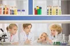 Écoliers dans des manteaux de laboratoire étudiant ensemble photo stock