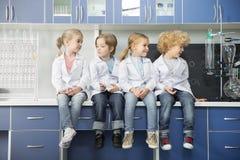 Écoliers dans des manteaux de laboratoire se reposant ensemble photographie stock