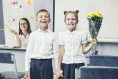 Écoliers de beaux enfants avec des fleurs pour les professeurs Photos libres de droits