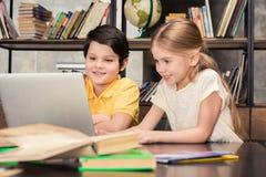 Écoliers de sourire étudiant ensemble et à l'aide de l'ordinateur portable Photographie stock libre de droits