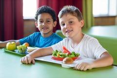 Écoliers de sourire ayant le repas Images libres de droits
