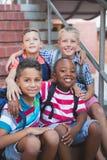 Écoliers de sourire se reposant sur l'escalier à l'école Photographie stock