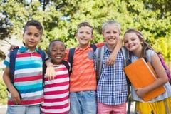 Écoliers de sourire se tenant avec des bras autour dans le campus Image stock