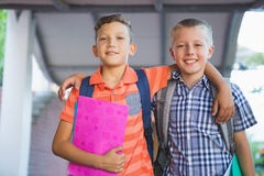 Écoliers de sourire se tenant dans le couloir Image libre de droits