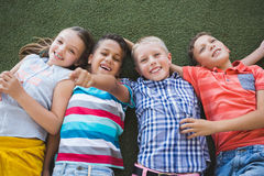 Écoliers de sourire se trouvant sur l'herbe dans le campus Images libres de droits
