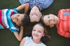 Écoliers de sourire se trouvant sur l'herbe dans le campus Image stock