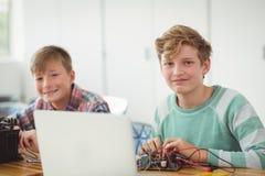 Écoliers de sourire travaillant sur le projet électronique dans la salle de classe Image libre de droits