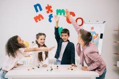 Écoliers donnant la haute cinq tout en étudiant avec le modèle moléculaire dans la salle de classe Images stock