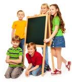 écoliers et écolières avec le tableau noir Images stock