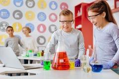 Écoliers fascinés observant la réaction chimique pendant la classe Photos stock