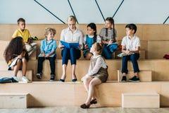 écoliers heureux adorables écoutant leur professeur tout en se reposant images stock