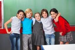 Écoliers heureux avec des bras autour de la position Images stock
