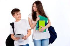 Écoliers heureux avec des sacs à dos sur un fond blanc Image stock