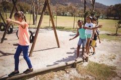 Écoliers heureux jouant dans le terrain de jeu Image libre de droits