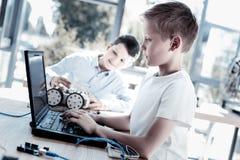 Écoliers intelligents travaillant sur l'ordinateur portable après la construction du robot Images libres de droits