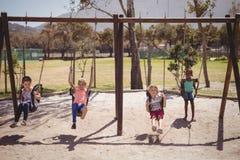 écoliers jouant dans le terrain de jeu Images libres de droits