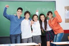 Écoliers joyeux se tenant ensemble dedans Photos stock