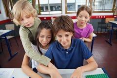 Écoliers mignons à l'aide de l'ordinateur portable au bureau Photo libre de droits