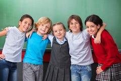 Écoliers mignons avec des bras autour de la position Image libre de droits