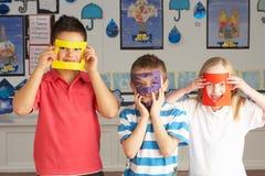 Écoliers primaires coupant des formes Photos libres de droits