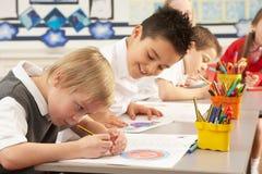 Écoliers primaires dans le fonctionnement de salle de classe Images stock