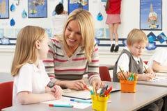 Écoliers primaires et professeur ayant une leçon images libres de droits