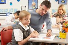 Écoliers primaires et professeur ayant une leçon Photos libres de droits