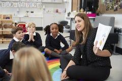 Écoliers primaires s'asseyant sur le plancher dans la salle de classe avec leur professeur supportant un livre pour les montrer,  images stock
