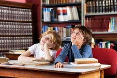 Écoliers réfléchis s'asseyant dans la bibliothèque Image stock
