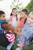 Écoliers remontant leurs mains dans le campus Images stock