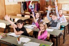 Écoliers soulevant des mains Images libres de droits