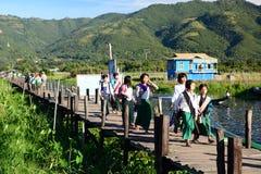 Écoliers sur le pont en bois Village de Maing Thauk Lac Inle myanmar photos stock