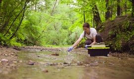 Écologiste de femme prélevant des échantillons de l'eau de The Creek photo stock